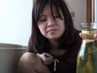 Asian babe pees at hand vase