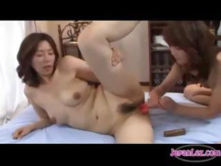 Two Asian battalion licking, categorization and shacking up their pussies with a double-headed dildo