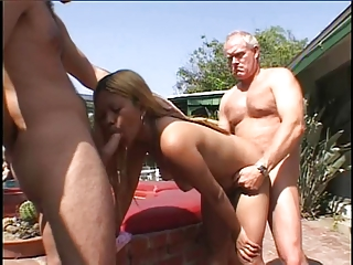 Blonde bimbo sucks and takes two cocks outdoors